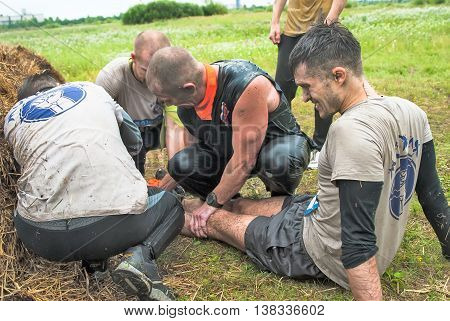 Tyumen, Russia - August 8, 2015: Steel Character extrim race on Krugloe lake. Gagarin park in Cape district. Members of team give first aid to companion after unsuccessful attempt at stage