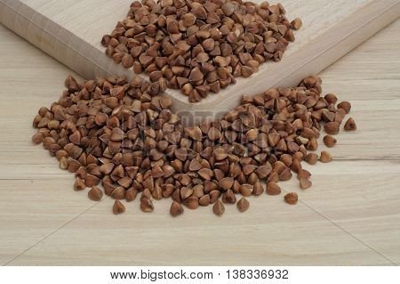 buckwheat scattered on two bright wooden boards