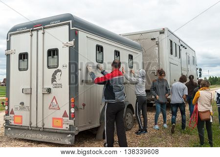 Tyumen, Russia - June 24, 2016: The 5th open championship of Russia on a plowed land. People load horses into van for transportation