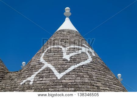 Detail of a stone traditional trulli house roof with a heart painted on it in white paint under a clear blue sky in the town of Alberobello in Puglia southern Italy.