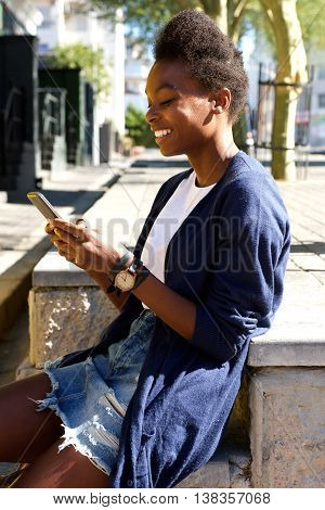 Happy Young Woman Sitting Outdoors And Using Cell Phone