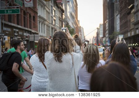 NEW YORK-JULY 12, 2016: People take photos of ManhattanHenge by standing on 23rd St for the occurrence when the setting sun aligns with the city street grid directly between buildings on July 12 2016.