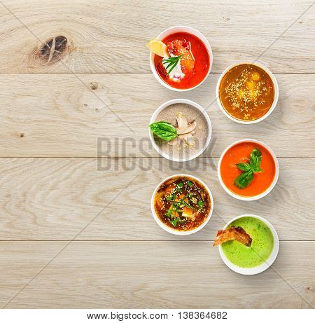 Variety of restaurant hot dishes, healthy food. Japanese miso, asian fish soup, russian borscht, english pea soup with bacon, mushroom soup, spanish gazpacho at wood, top view with copy space