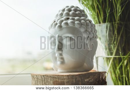 Zen spiritual ritual meditating white face of Buddha on green floral background. Religion concept esoterics. Still life rustic style. Home decor. Place for text copy space