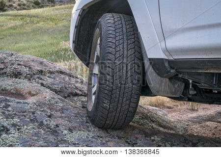 Closeup of 4x4 SUV car driving on a rocky trail in mountains