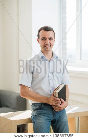 Closeup portrait, young business man or teacher in blue shirt reading, perusing books at school library class.
