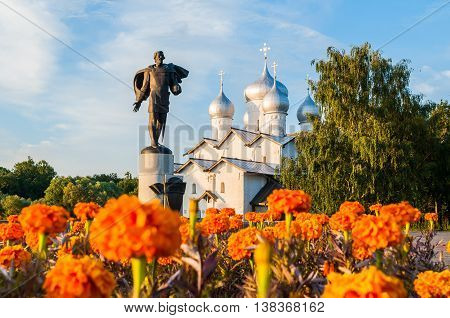 VELIKY NOVGOROD RUSSIA - JUNE 21 2016. Monument to prince Alexander Yaroslavich Nevsky on the background of Boris and Gleb Church with defocused camomiles on the foreground. Architecture landscape