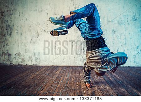 Young man break dancing on wall background. Vibrant colors effect.