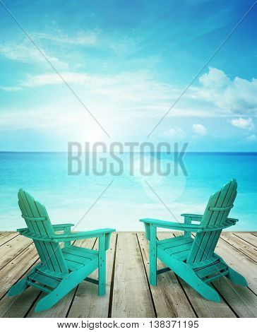 Wood pier with sun chairs and ocean in background