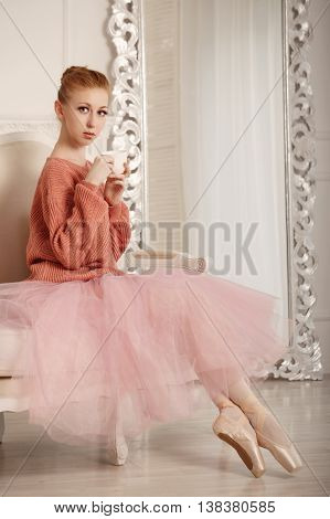 Pretty young ballerina tea drinkers. Ballerina in tutu and pink sweater. Time to drink tea.