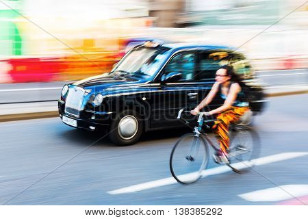 Cyclist And London Taxi In Motion Blur In The City Traffic Of London, Uk