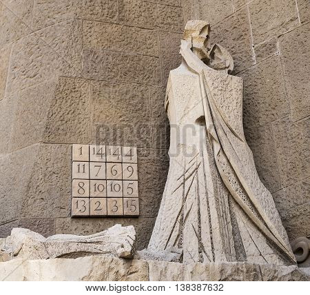 BARCELONA, SPAIN - APRIL 18, 2015: A scene on the Passion Facade of the Sagrada Familia portrays Judas kissing Jesus. The numbers in the Subircahs Magic Square sum up to 33 across any line and this alludes to the age of Jesus at the time.