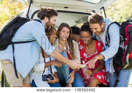 Group of happy friends looking at mobile phone on a sunny day
