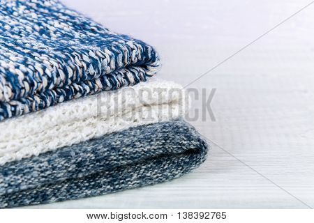 Wool socks and stack of various sweaters. Winter style. On a wooden table, handmade
