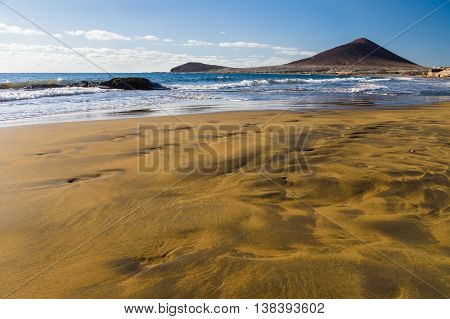 Brown-yellow sand of Playa el Medano beach Montana Roja mountain on background Tenerife Canary islands Spain
