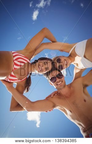Portrait of happy young friends forming huddle against sky