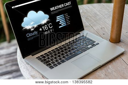technology, weather cast, business and modern life concept- close up of open laptop computer with meteo forecast on screen on table at hotel terrace