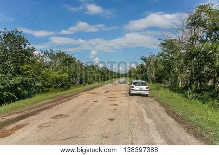 VINALES, CUBA - SEPTEMBER 27, 2007: Road with many potholes in the backcountry of Cuba