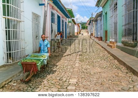 TRINIDAD, CUBA - SEPTEMBER 28, 2007: Old man with a cart of vegetables on a cobblestoned street in Trinidad, Cuba
