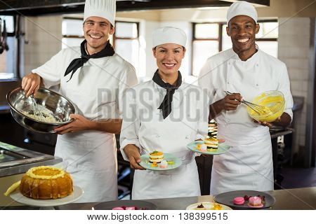 Portrait of chefs preparing a dessert in commercial kitchen