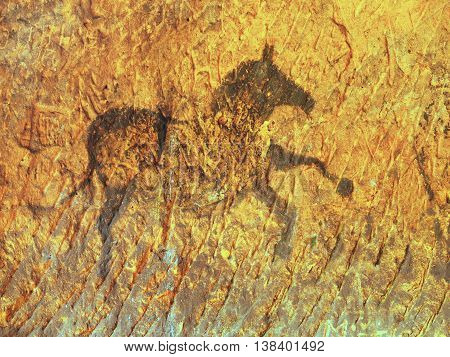 Abstract art in sandstone cave. Black carbon paint of horses on sandstone wall, copy of prehistoric picture.