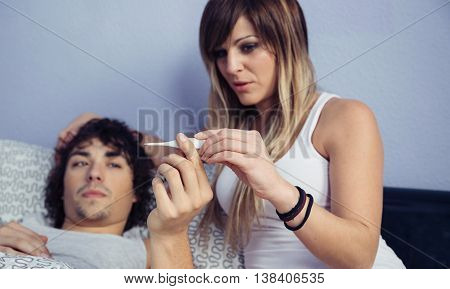 Portrait of young woman looking temperature of sick man in thermometer. Sickness and healthcare concept.