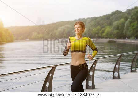 Sportswoman listening to music and running outdoors. Image with lensflare