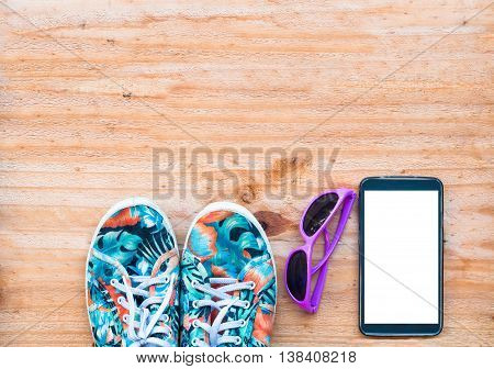 The Canvas Shoe With Sunglasses And Mobile Phone On Wooden Background. Accessories For Travelling
