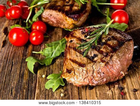 Delicious beef steak. Succulent thick juicy portions of grilled fillet steak served with tomatoes and roast vegetables on an old wooden board
