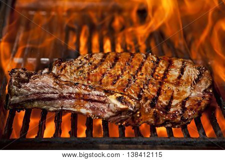A top sirloin steak flame broiled on a barbecue, shallow depth of field.