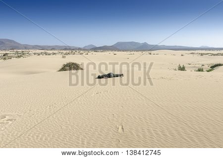 Woman fainted in desert sand. She is lying in the sand.