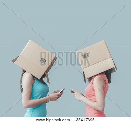 Adolescent girls with boxes on their heads texting with their smart phones social networks and isolation concept