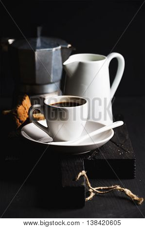 Italian coffee set for breakfast. Cup of hot espresso, creamer with milk, cantucci and moka pot on dark rustic wooden board over black background, selective focus, vertical composition