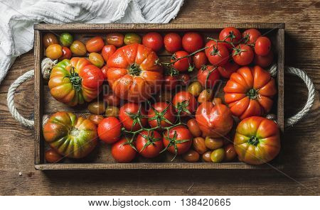 Colorful assortment of heirloom, bunch and cherry tomatoes in wooden tray over rustic wooden background, top view, horizontal composition
