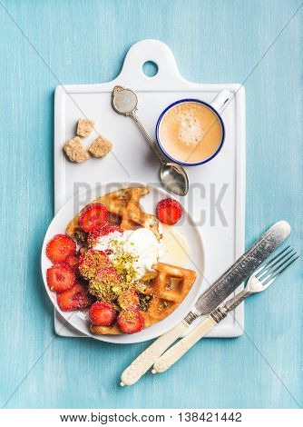 Breakfast set. Warm homemade belgium waffles with whipped cream, strawberry, maple syrup and crushed pistachios, cup of espresso and cubes of brown sugar on white ceramic board over blue painted wooden background, top view, vertical composition