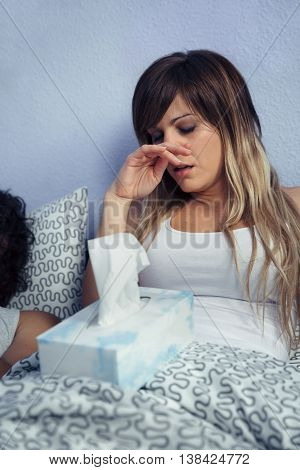 Portrait of young sick woman with tissues box sitting on bed. Sickness and healthcare concept.