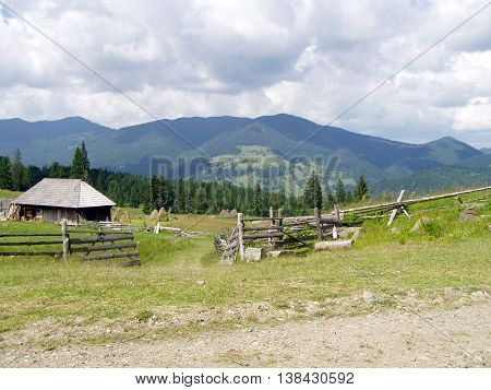 View of mountain walley with little wooden house