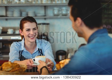 Cheerful female barista giving coffee to customer at cafeteria