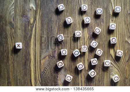 One against all, concept photo, flat lay. Concept of business success. Uniqueness, independent, dissent, think differently. Wooden tic tac toe. XO.