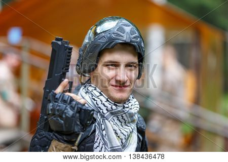 Smart boy in opened mask with paintball handgun