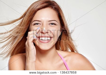 Young attractive girl smiles and rubs his nose on the cream. Gray background.