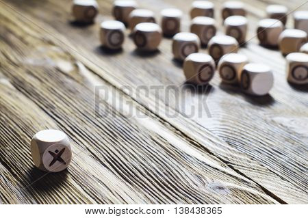 One against all concept photo. Concept of business success. Uniquenessindependentdissentthink differently. Wooden tic tac toe. XO.