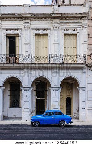 HAVANA, CUBA - MARCH 17, 2016: Blue car parking in front of old buildings in Paseo de Marti in Havana the capital of Cuba