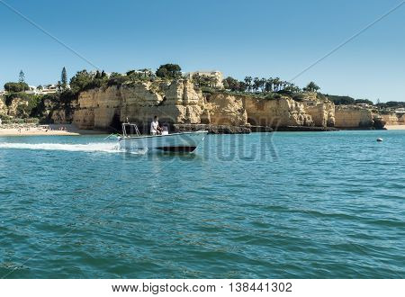 ALGARVE COAST PORTUGAL - MAY 19: A view of a small boat with a man on the board near the coast Algarve in Portugal 2016