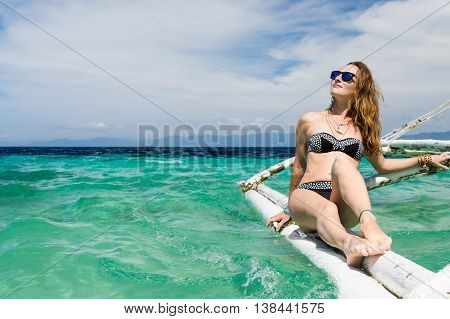 young european woman with sunglasses is sitting on the boat in tropical turquoise sea and getting tan at sunny day ander blue sky
