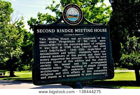 Rindge New Hampshire - July 13 2013: Town sign tells the history of the colonial-era 1796 Meeting House church on the Village Green