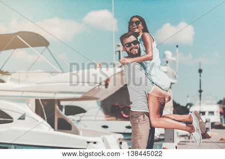 Unleashed fun. Cheerful young man picking up his beautiful girlfriend while standing on quay