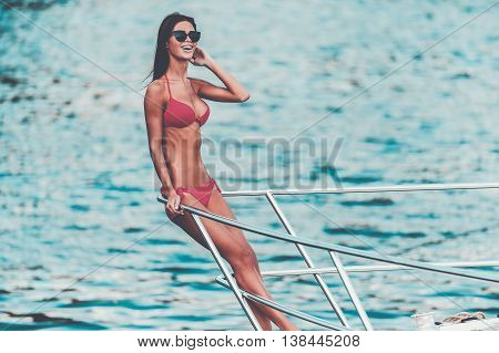 Summer relaxation. Smiling young woman leaning at the handrail and looking away while standing on the ship's bow