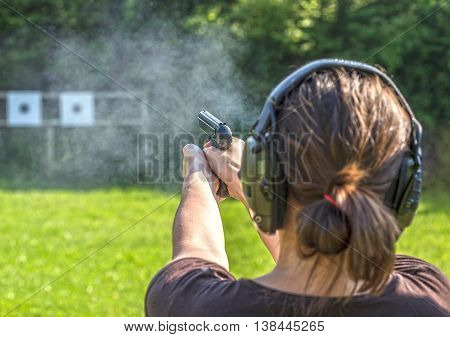 Girl shooting with a gun on a training course.