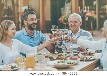 Cheers to family! Happy young and senior couples sitting at the dining table and toasting with wine